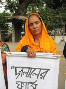 Bangladesh.Trafficking human chain._Selina Begum, 60, whose son is still missing, holding a placard saying hang trafficking traders.6.15.Mushfique Wadud