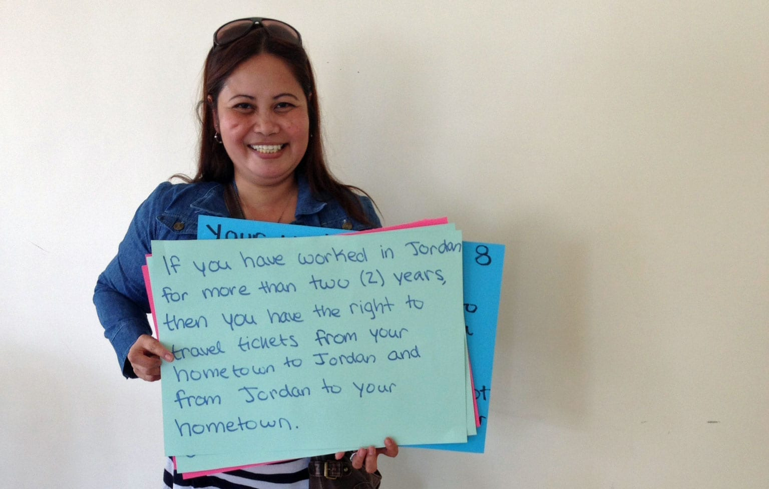 Filipina domestic worker participant, holding sign, if you have worked in Jordan for more than two years, then you have the right to travel tickets from your hometown to Jordan and from Jordan to your hometown