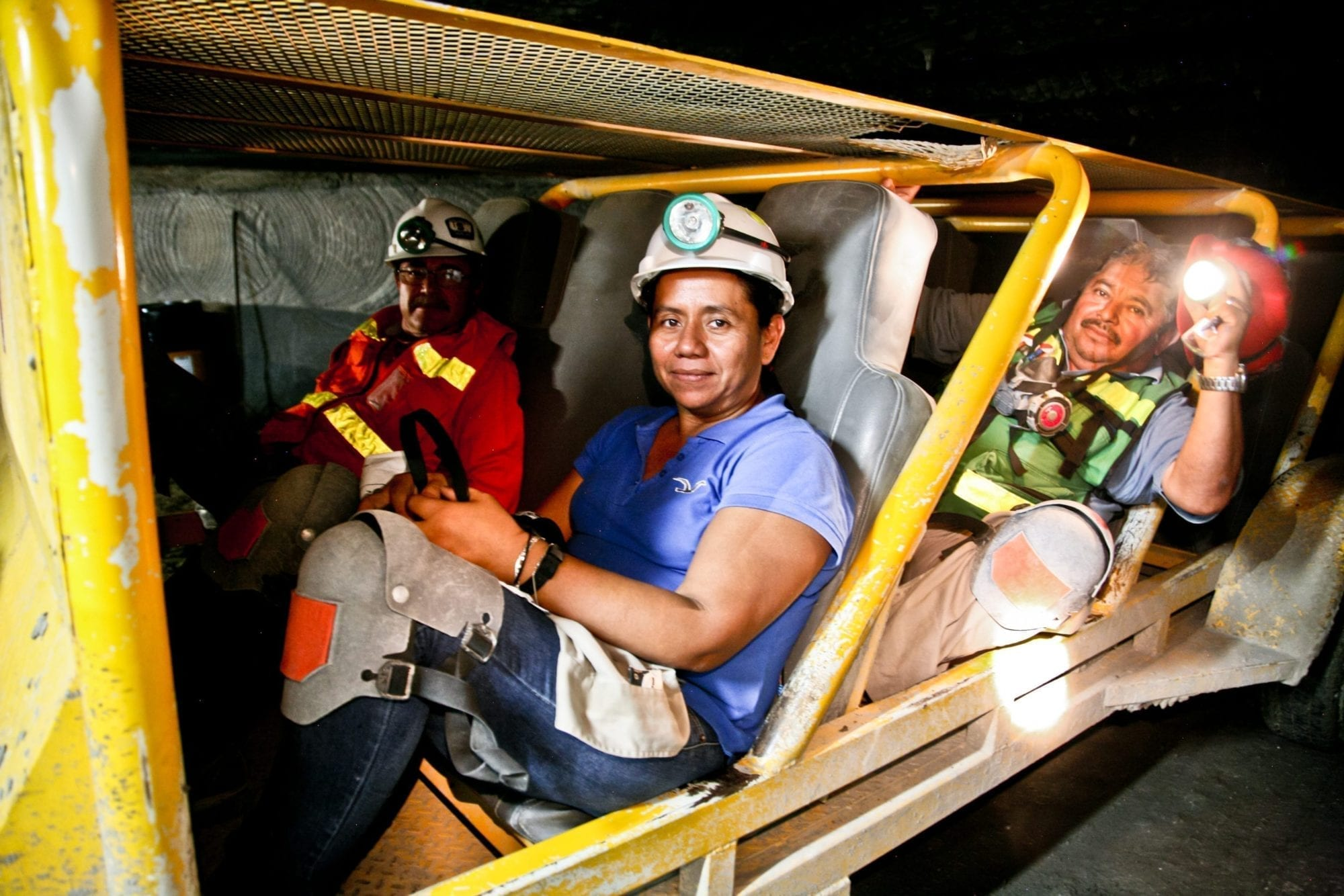 Ruth Rivera and her co-workers travel through the mines in a cart that transports all personnel.