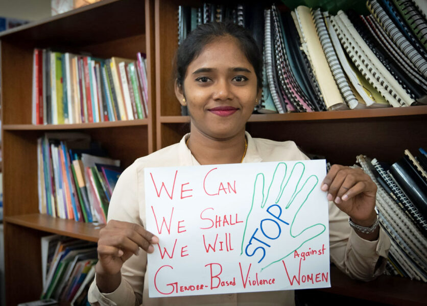Sri Lanka Womens' Committee with Prithvi Sharujha from the Lanka Eksath Jathika Workers Union and sign saying end gender-based violence, worker rights, Solidarity Center